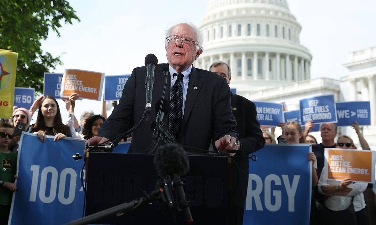 U.S. Senator Bernie Sanders speaking at podium in front a crowd with the U.S. Capitol building visible in the background.