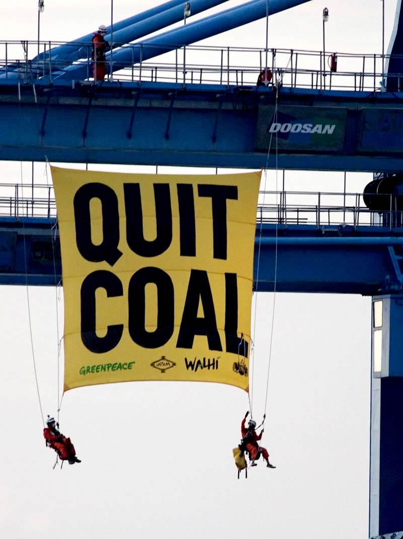 Activists hanging a gigantic 'End Coal' banner from a large coal-loading crane in Cirebon, West Java, Indonesia.