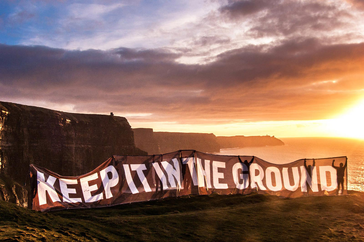 People holding up a large-scale banner that reads 'Keep it in the Ground' along a scenic oceanside cliff.