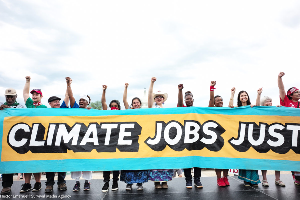 Row of people holding a teal and gold banner that says 'Climate Jobs Justice' at the 2017 People's Climate March in Washington DC